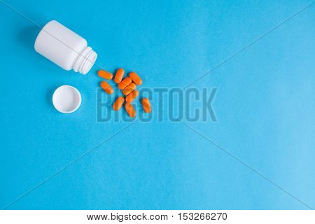orange tablets in plastic container on blue background top view