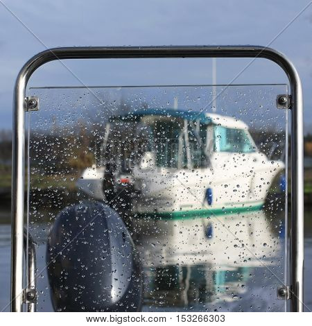 motor boat in the harbor as seen through glass covered with water droplets