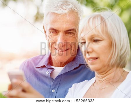 Happy senior couple looking at smartphone