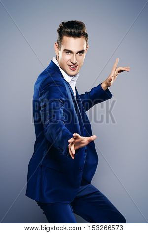 Elegant young man dancing at studio with expression.