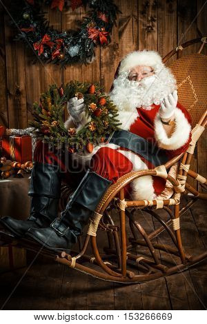 Santa Claus sitting in his wooden house in a comfortable chair and prepare gifts for Christmas. He is holding a Christmas wreath.