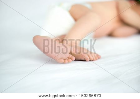 Close up of tiny sweet feet of sleeping newborn kid lying on white bed. Concept image