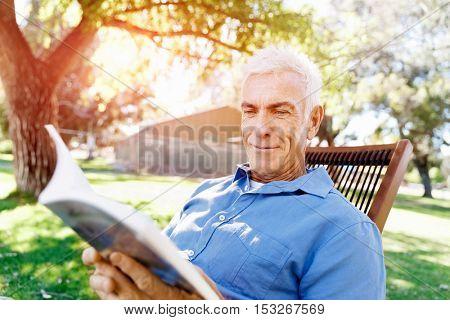 Senior man sittingin park while reading book