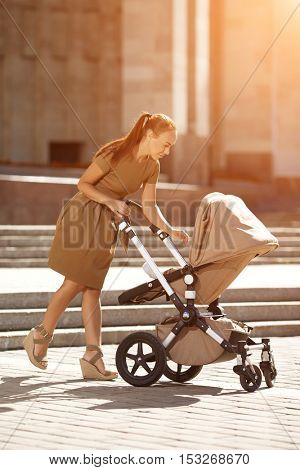 Fashionable modern mother on a urban street with a pram. Young mother walks with a child in the city. Beautiful young woman with a child in a baby carriage