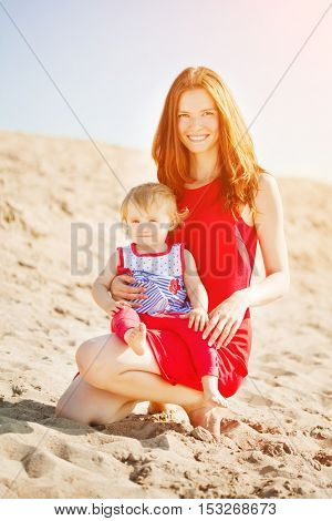 Beautiful Mom and baby outdoors. Happy family playing on the beach. Mom and baby. 