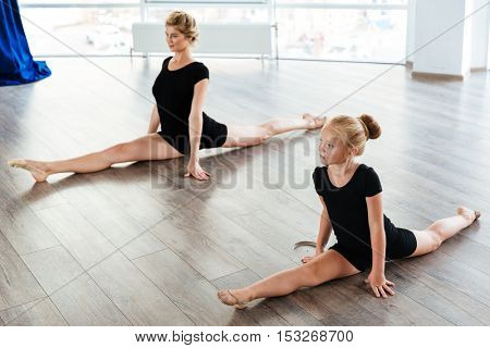 Beautiful little girl ballerina and her teacher doing twine in ballet class