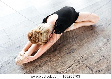 Beautiful little girl ballerina stretching on the floor in dance studio