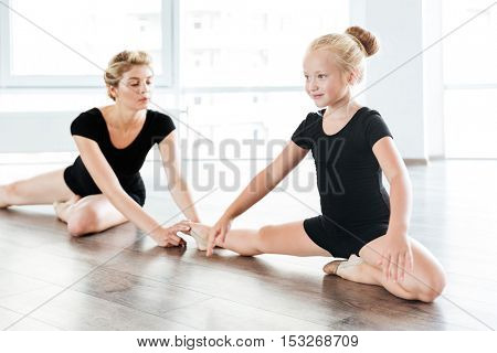 Happy little girl ballerina sitting and stretching legs with teacher in ballet school