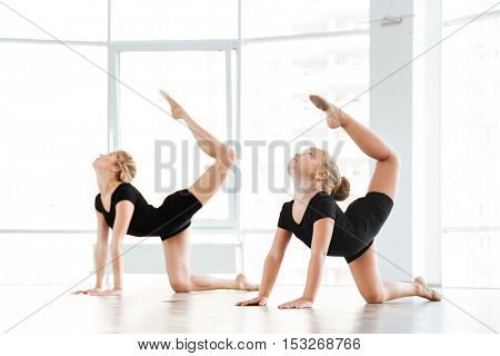 Cute little girl ballerina and her teacher doing exercises in ballet class