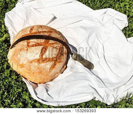 Loaf of bread and hammer on grass