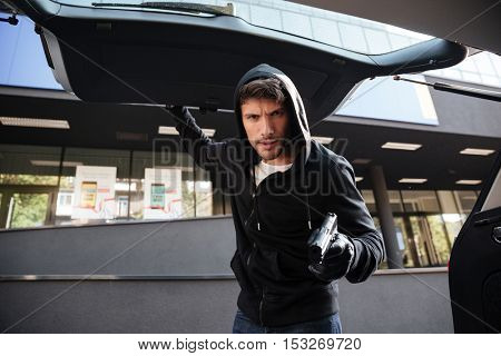 Dangerous criminal man in hoodie threatening with gun and closing car trunk outdoors