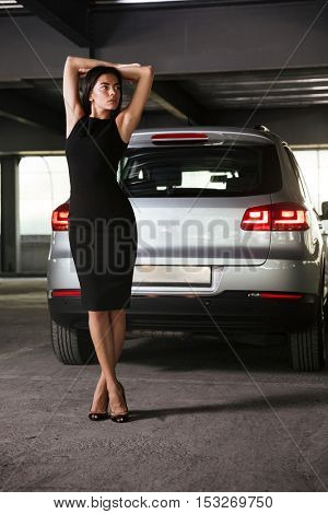 Attractive relaxed young businesswoman standing near her car on parking