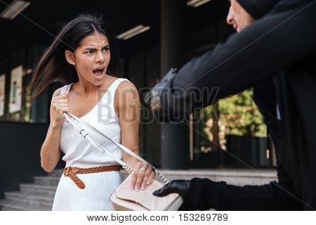 Angry young woman shouting and protecting from man thief with gun on the street