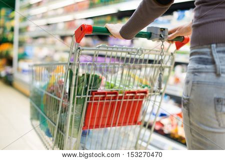 Detail of a woman driving her shopping cart in a grocery store