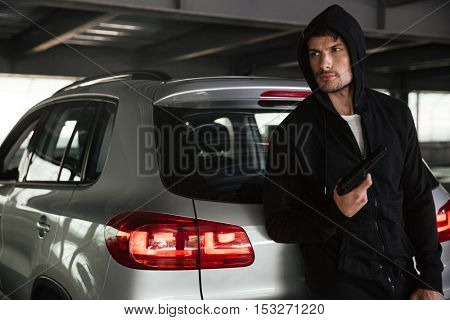 Criminal man in black hoodie with gun standing near car on parking
