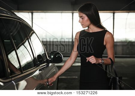 Beautiful young businesswoman opening the door of her car on parking