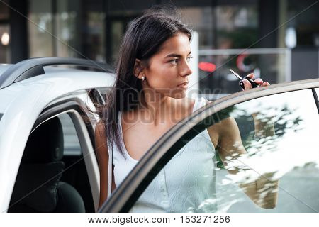 Attractive young woman standing near opened car outdoors