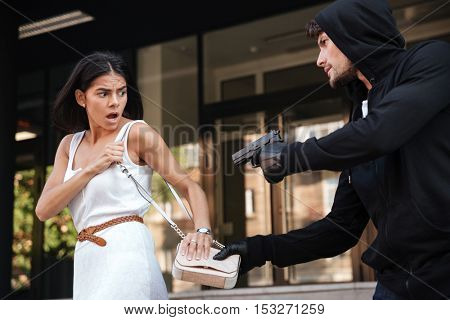 Criminal man with gun stealing bag of scared young woman on the street