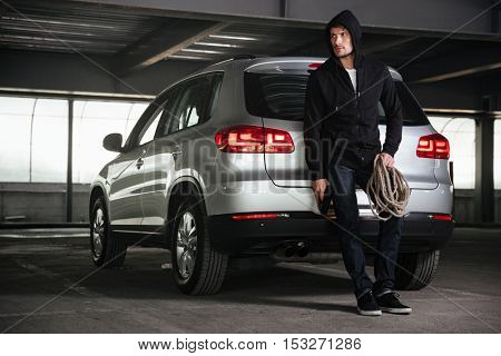 Criminal young man in hoodie standing and holding gun and rope on car parking