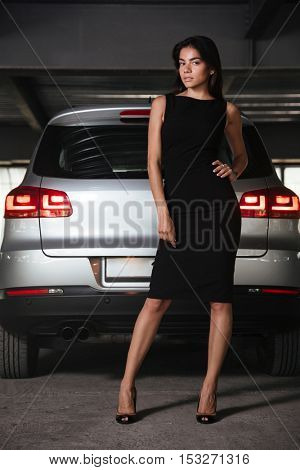 Portrait of confident young business woman in black dress standing near her car on parking