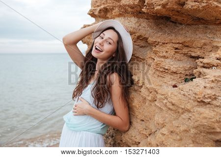 Happy attractive young woman standing near the rock on the beach