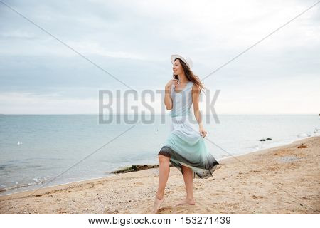 Smiling attractive young woman in white hat and dress walking on the beach