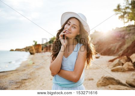 Smiling beautiful young woman in hat standing on the beach