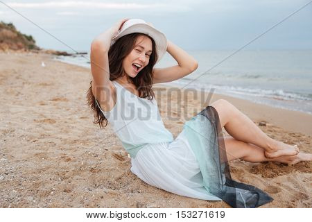 Cheerful playful young woman in white hat and dress sitting and winking on the beach