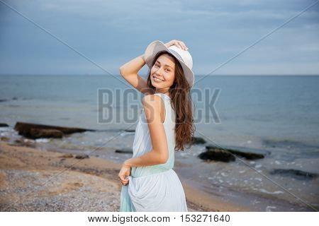 Happy beautiful young woman in hat walking on the beach