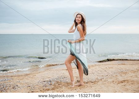 Happy lovely young woman in hat and dress standing on the beach