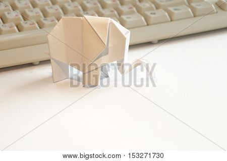 Paper origami elephant isolated on white background on the table next to the computer keyboard