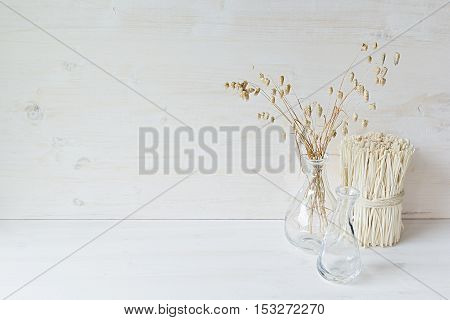 Soft home decor of glass vase with spikelets and stalks on white wood background. Interior.