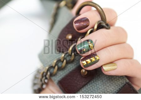 Short manicure brown green with metallic gold rhinestones and chain in a female hand.