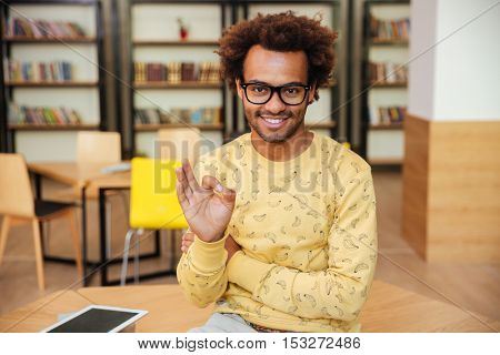 Cheerful african young man in glasses sitting and showing ok sign in library