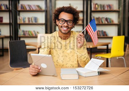 Portrait of cheerful african american young man holding US flag and using tablet in library