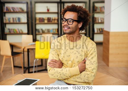 Confident african young man in glasses sitting with arms crossed and smiling in library