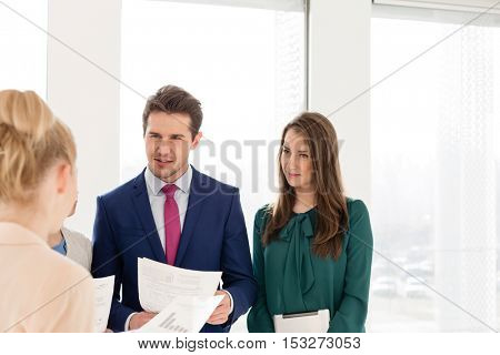 Young businessman with female colleagues discussing over documents in new office