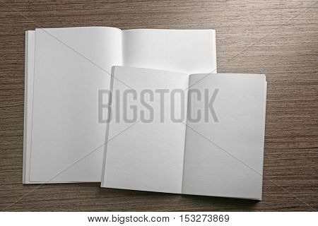 Blank open brochures on wooden background