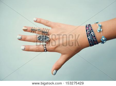 Female hand with jewelry on color background
