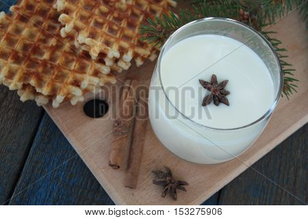 waffles with milk, cinnamon, anise on blue wooden background. a magical dessert for Christmas