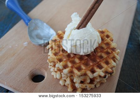 waffles with ice cream and milk, cinnamon, anise on blue wooden background. a magical dessert for Christmas