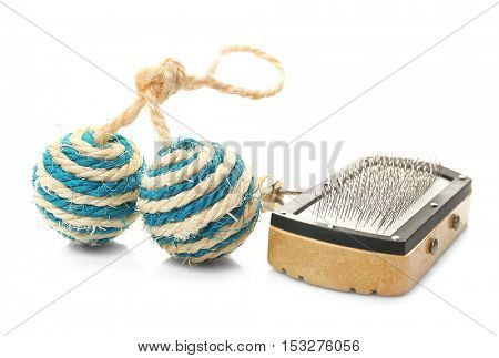 Grooming brush for pets and toy ball on white background