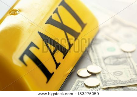 Yellow taxi roof sign with money, closeup