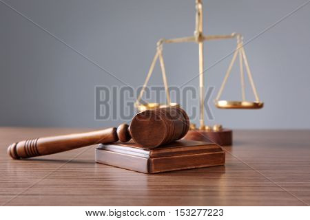 Judge's gavel and justice scales on wooden table and grey background