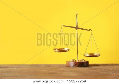 Justice scales on wooden table and  yellow background