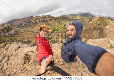 Couple with outstretched arms taking selfie on windy mountain summit in the majestic Golden Gate Highlands National Park South Africa. Concept of adventure and traveling people. Fish eye view.