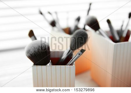 Set of makeup brushes in decorative boxes, closeup