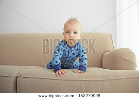 Adorable little baby crawling on sofa
