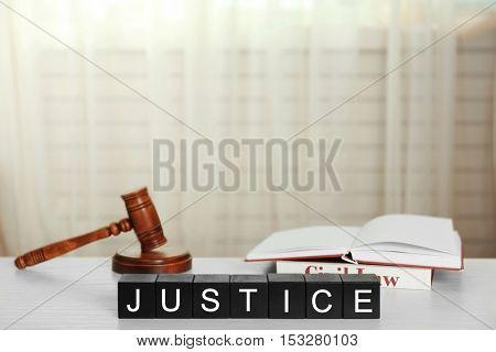 Black cubes with word JUSTICE and gavel on white table