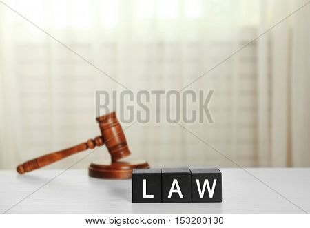 Black cubes with word LAW and gavel on white table